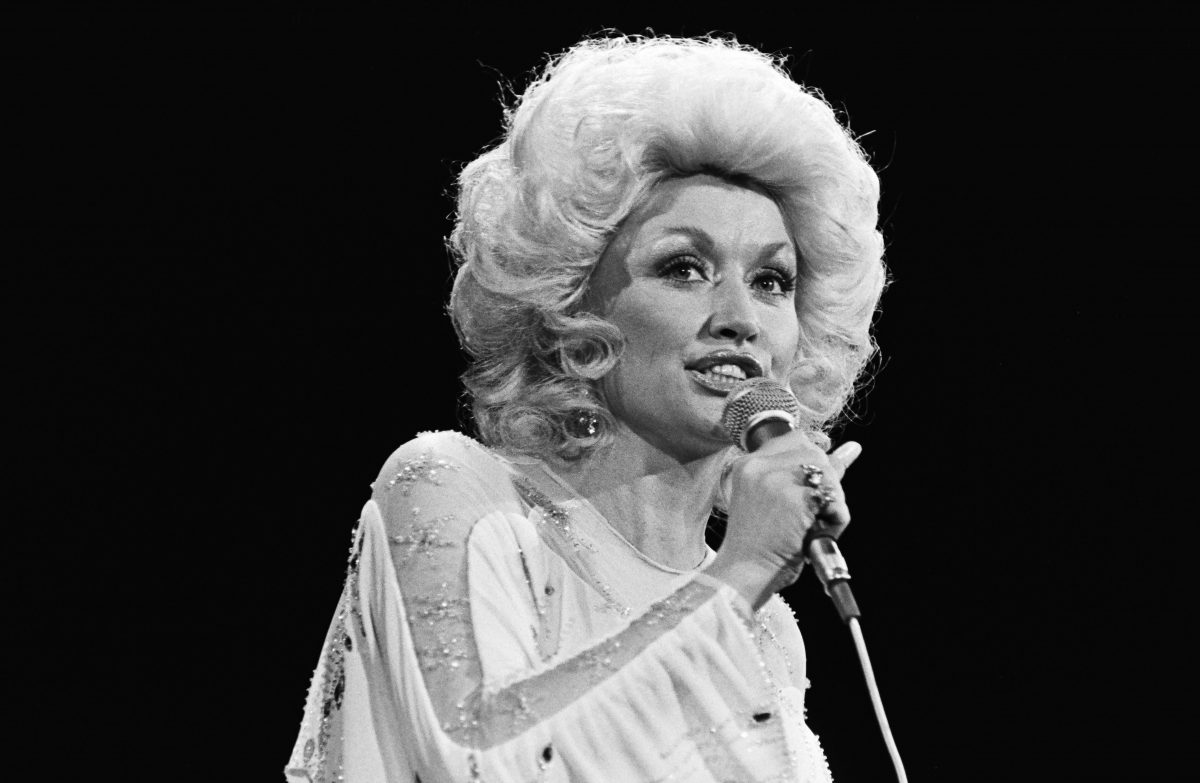 Dolly Parton singing into a microphone. The shot is black and white. The year is 1981.