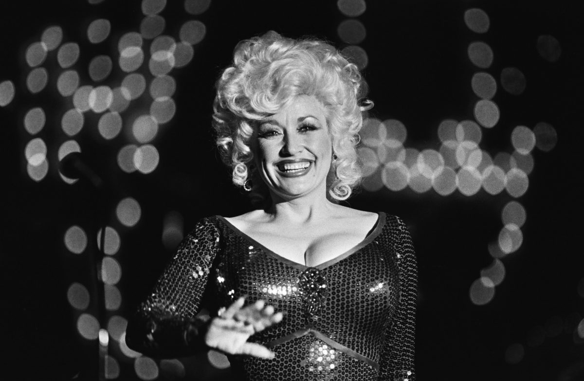 Dolly Parton performs at Harrah's Club in 1980. She's photographed in black and white, waving to the camera.