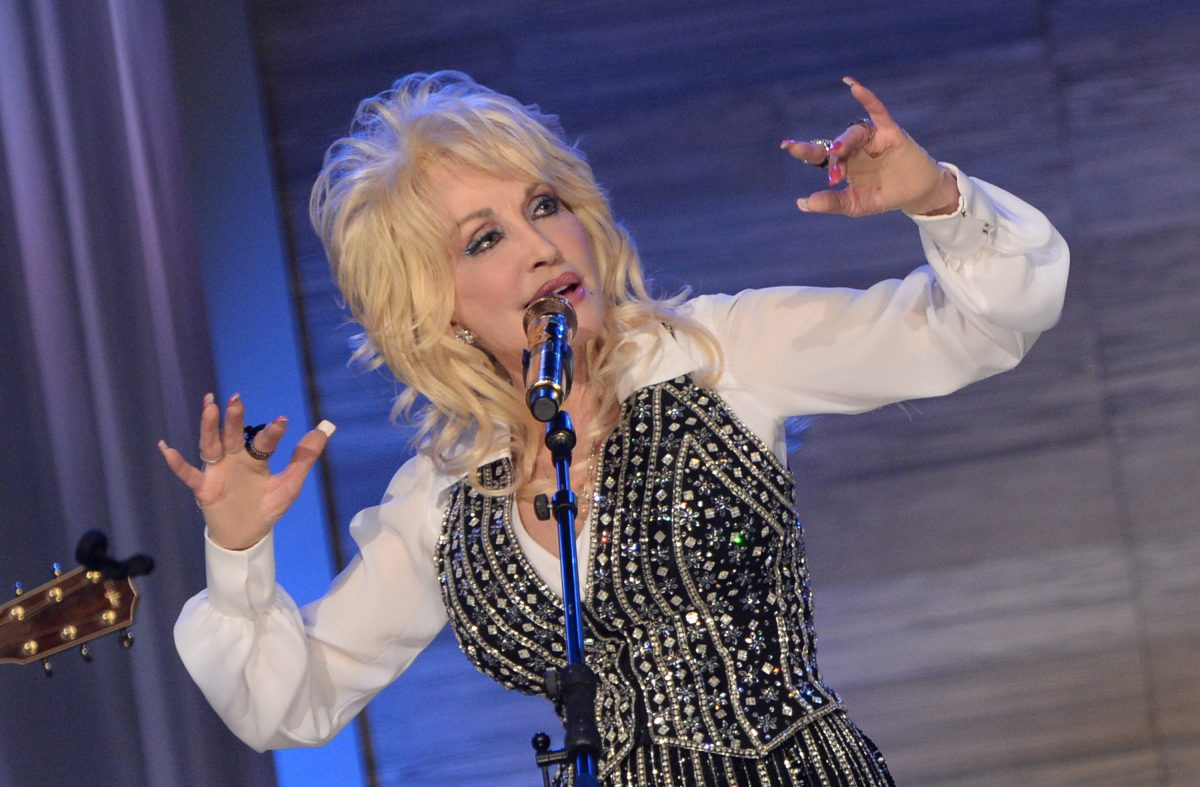 Dolly Parton sings into a microphone in a black vest and white blouse.