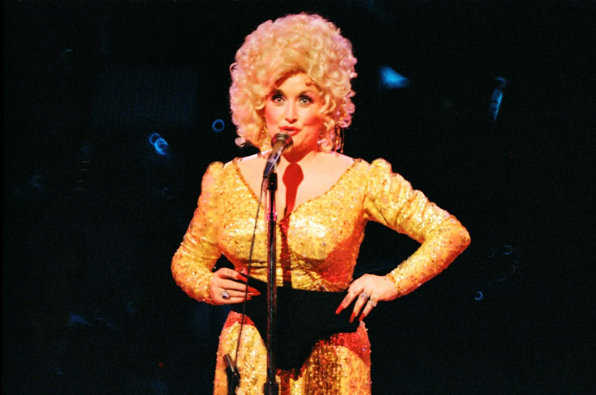 Dolly Parton stands on stage in a gold dress. She's speaking into a microphone and hold black underwear.