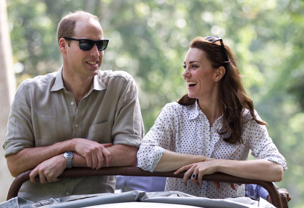 Prince William and Kate Middleton laughing in front of a blurred background