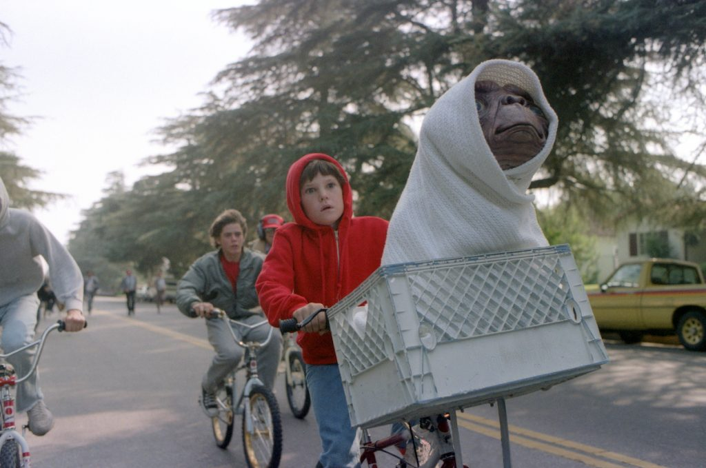 Henry Thomas wears a red hoodie and rides a bike with E.T. in a scene from 'E.T. the Extra-Terrestrial'