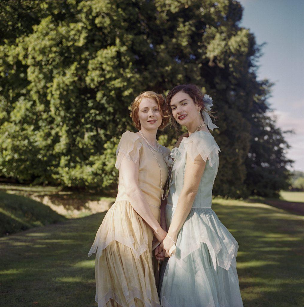 Emily Beecham as Fanny and Lily James as Linda, holding hands, in 'The Pursuit of Love'