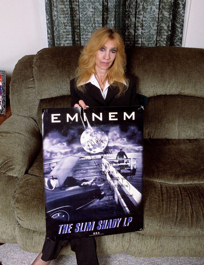 Eminem's mother Debbie Mathers holds a poster with a hand written message during a portrait session at her home