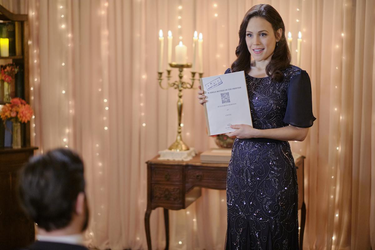 Erin Krakow as Elizabeth holding a copy of her novel manuscript in 'When Calls the Heart'
