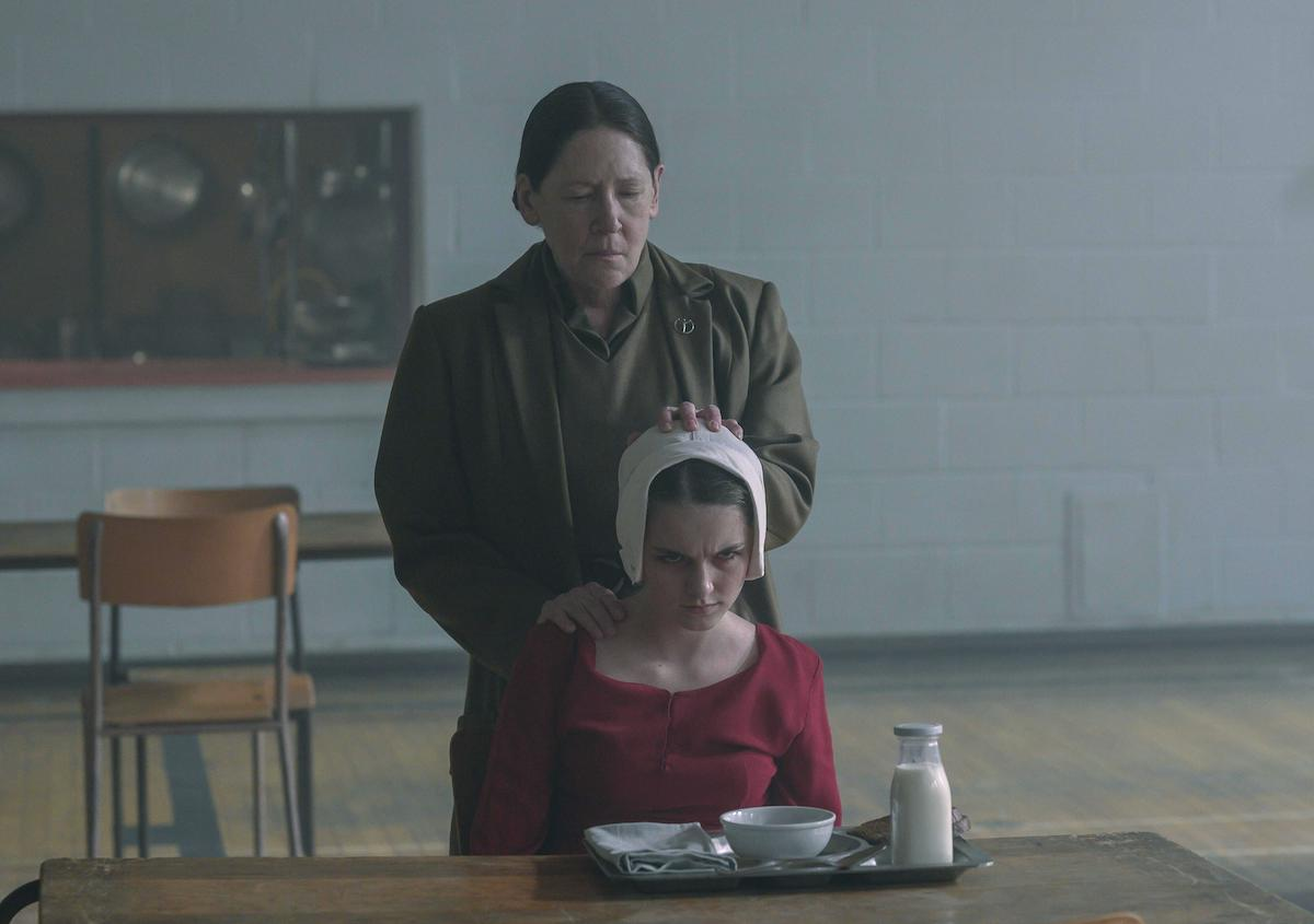 Ann Dowd as Aunt Lydia and Mckenna Grace as Esther Keyes in 'The Handmaid's Tale' Season 4. Dowd wears her brown Aunt uniform. Grace wears a red Handmaid dress and white bonnet.