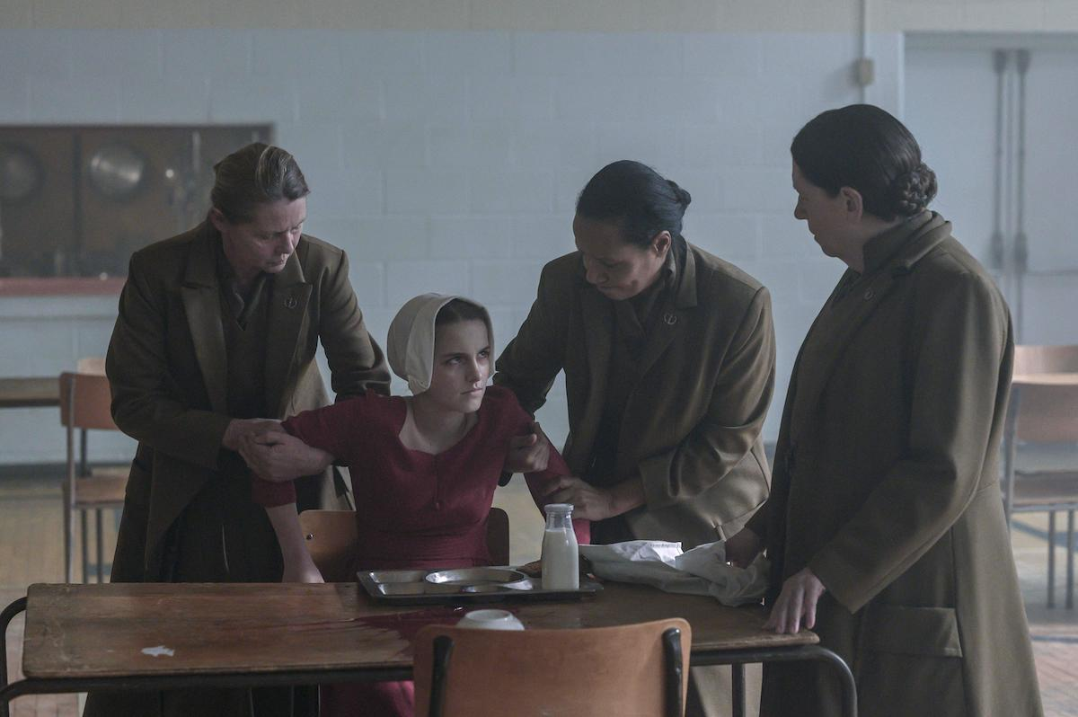 Mckenna Grace as Esther Keyes and Ann Dowd as Aunt Lydia in 'The Handmaid's Tale' Season 4. Grace's arms are held back by other Aunts as Aunt Lydia (Dowd) looks at her sternly.