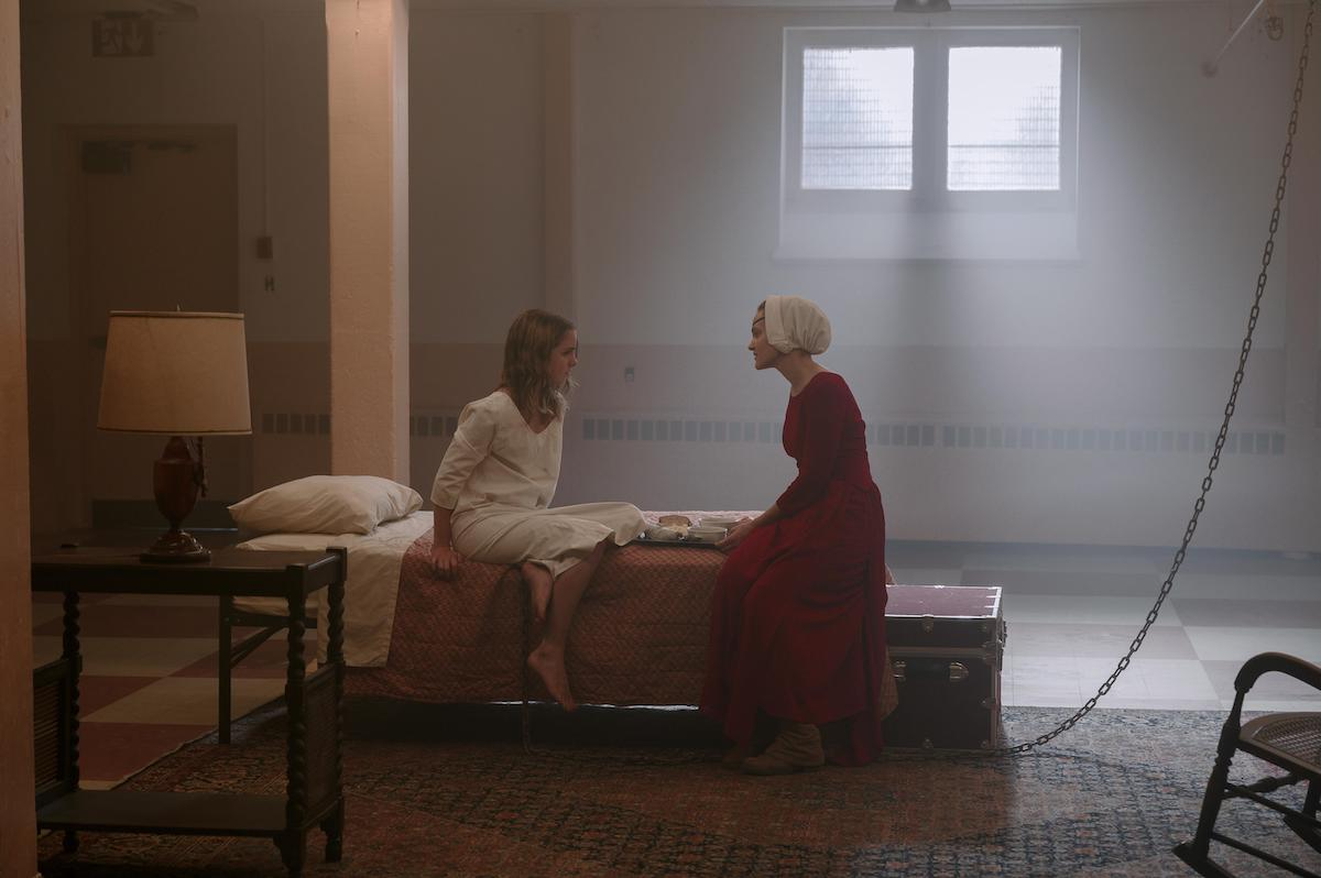 Mckenna Grace as Esther Keyes and Madeline Brewer as Janine in 'The Handmaid's Tale' Season 4. Grace wears a white nightgown and sits on a bed next to Brewer, who wears a red Handmaid dress and white bonnet. They're in a school cafeteria turned into a prison cell. A chain stretches from floor to ceiling next to the bed.