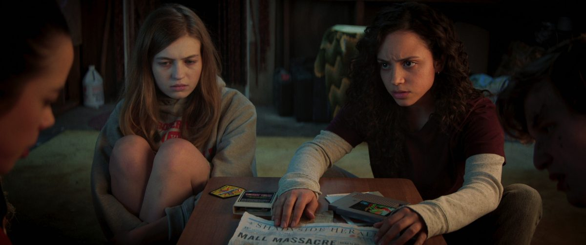 'Fear Street' stars Olivia Scott Welch and Kiana Madeira looking at a newspaper in Part 1 of the Netflix series