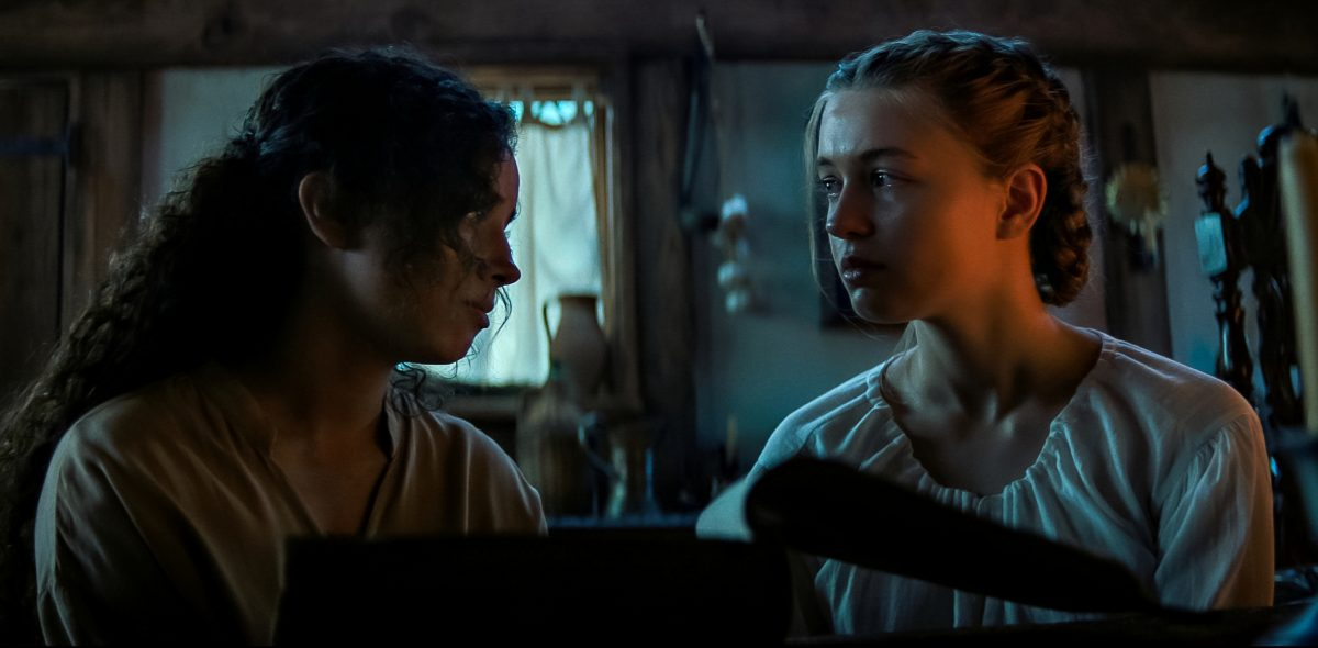Kiana Madeira and Olivia Scott Welch looking at one another in 'Fear Street Part 3: 1666'