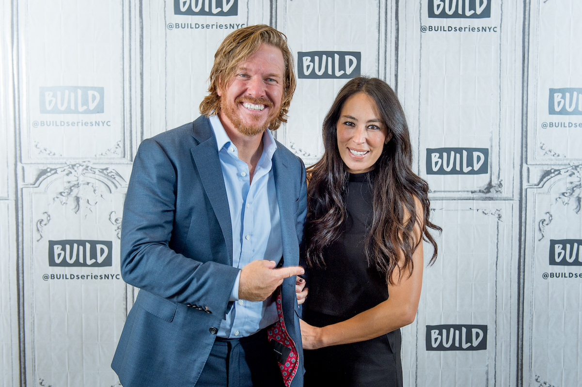 Chip Gaines points to Joanna Gaines as she holds onto his arm while they pose during a 2017 event.