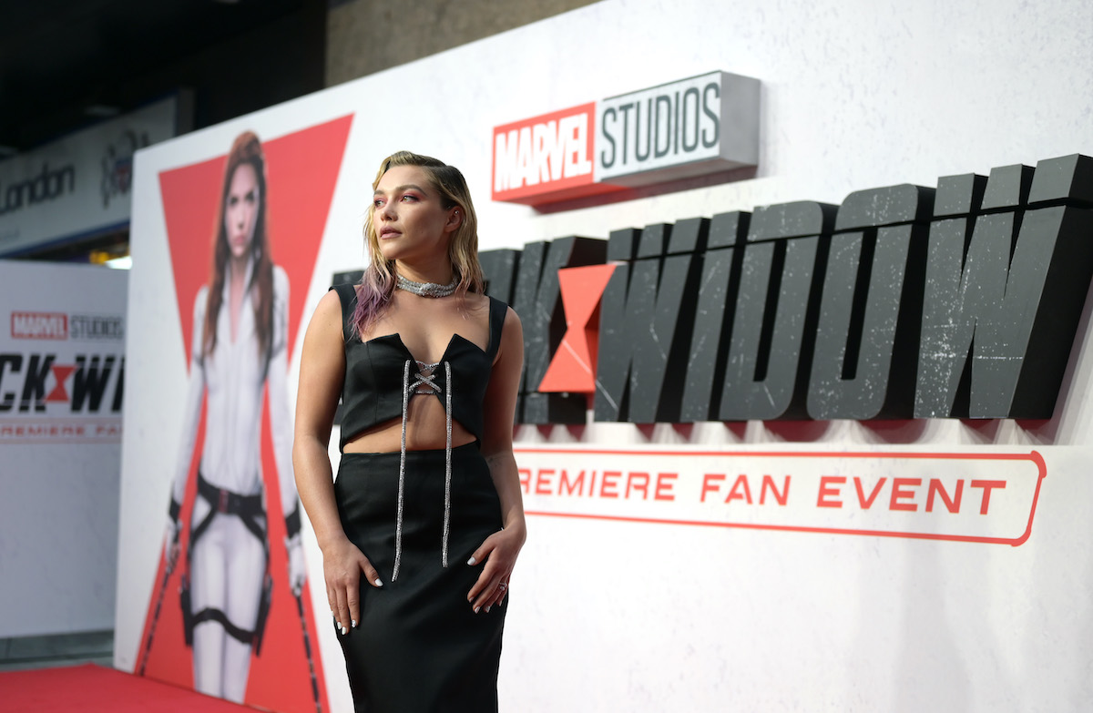 Florence Pugh wears black and stands in front of 'Black Widow' poster art
