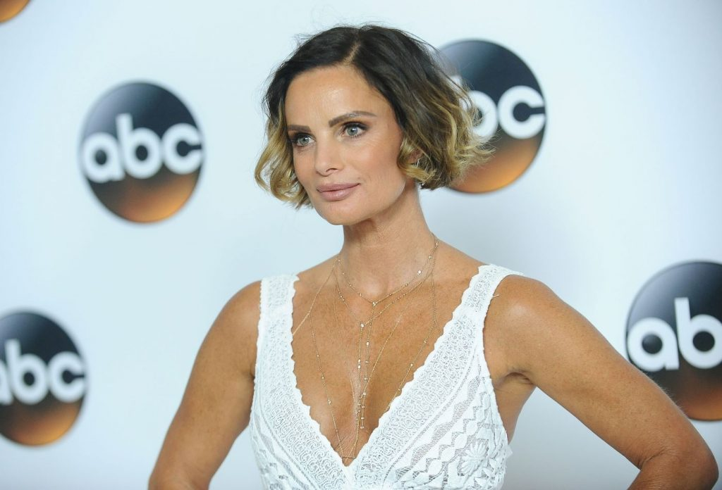 Gabrielle Anwar is wearing a white lace inspired dress with cut-off sleeves and a swooping neckline in front of a white background.