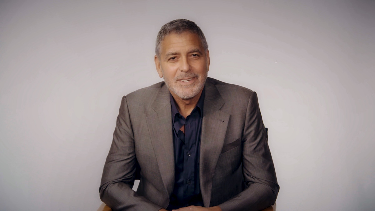 George Clooney sitting in a chair