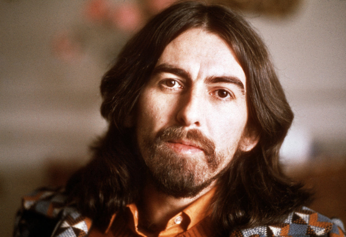 Former Beatle George Harrison faces the camera in a 1976 portrait sporting shoulder-length hair as well as a beard.