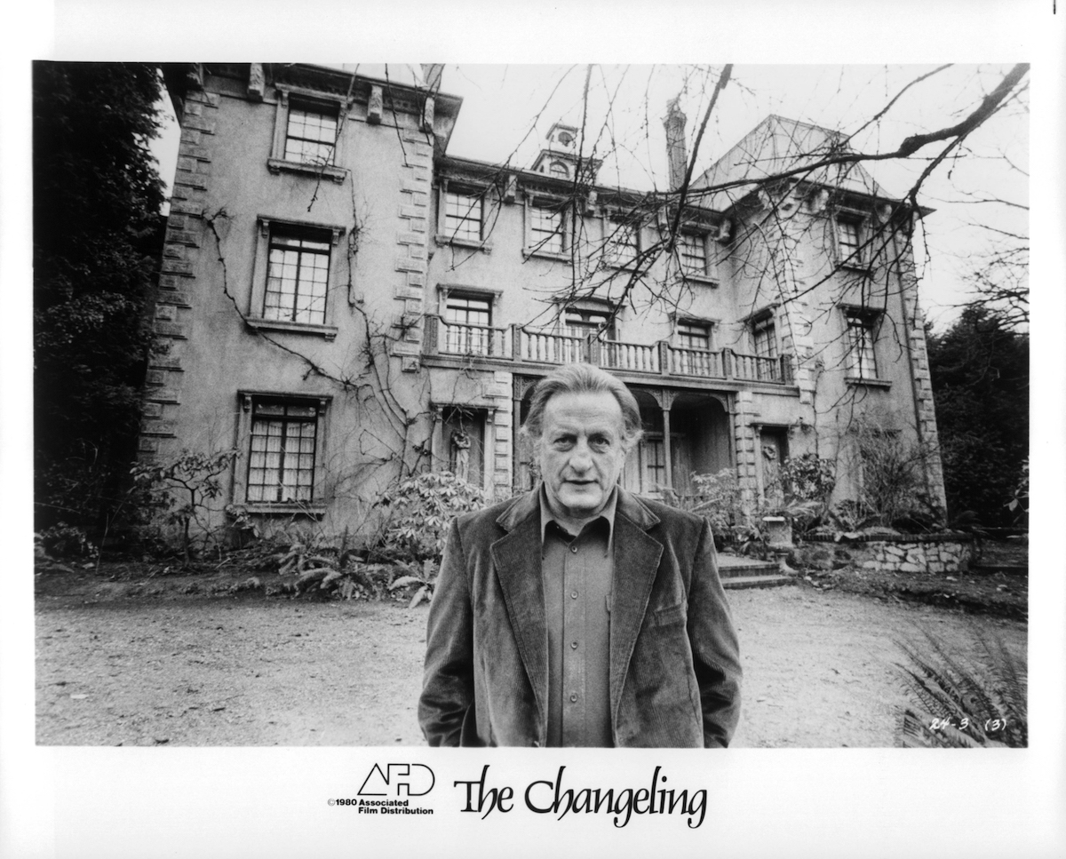 Actor George C. Scott standing in front of mansion