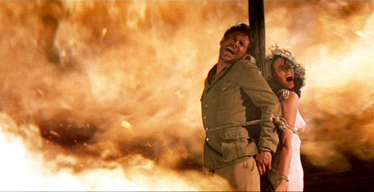 Harrison Ford as Indiana Jones and Karen Allen as Marion Ravenwood in 'Raiders of the Lost Ark'. They're tied to a stake as a fire burns behind them.
