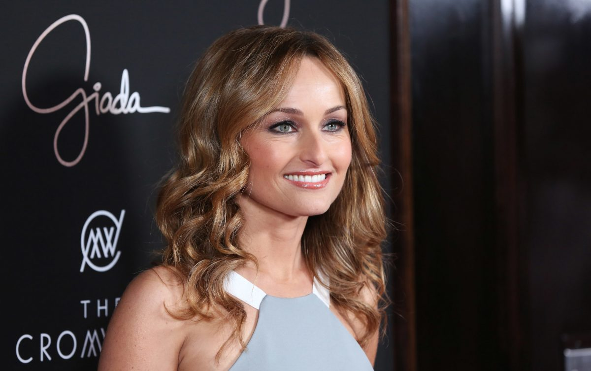 Food Network chef Giada De Laurentiis wearing a grey and white top and smiling at her restaurant opening
