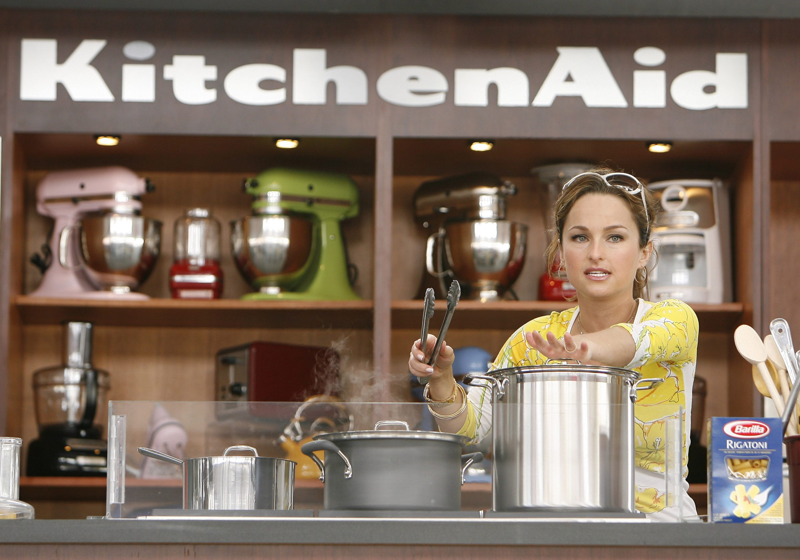 Celebrity chef Giada De Laurentiis wears sunglasses atop her head and a bright yellow and white three-quarter-sleeve top as she demonstrates preparation of a recipe.