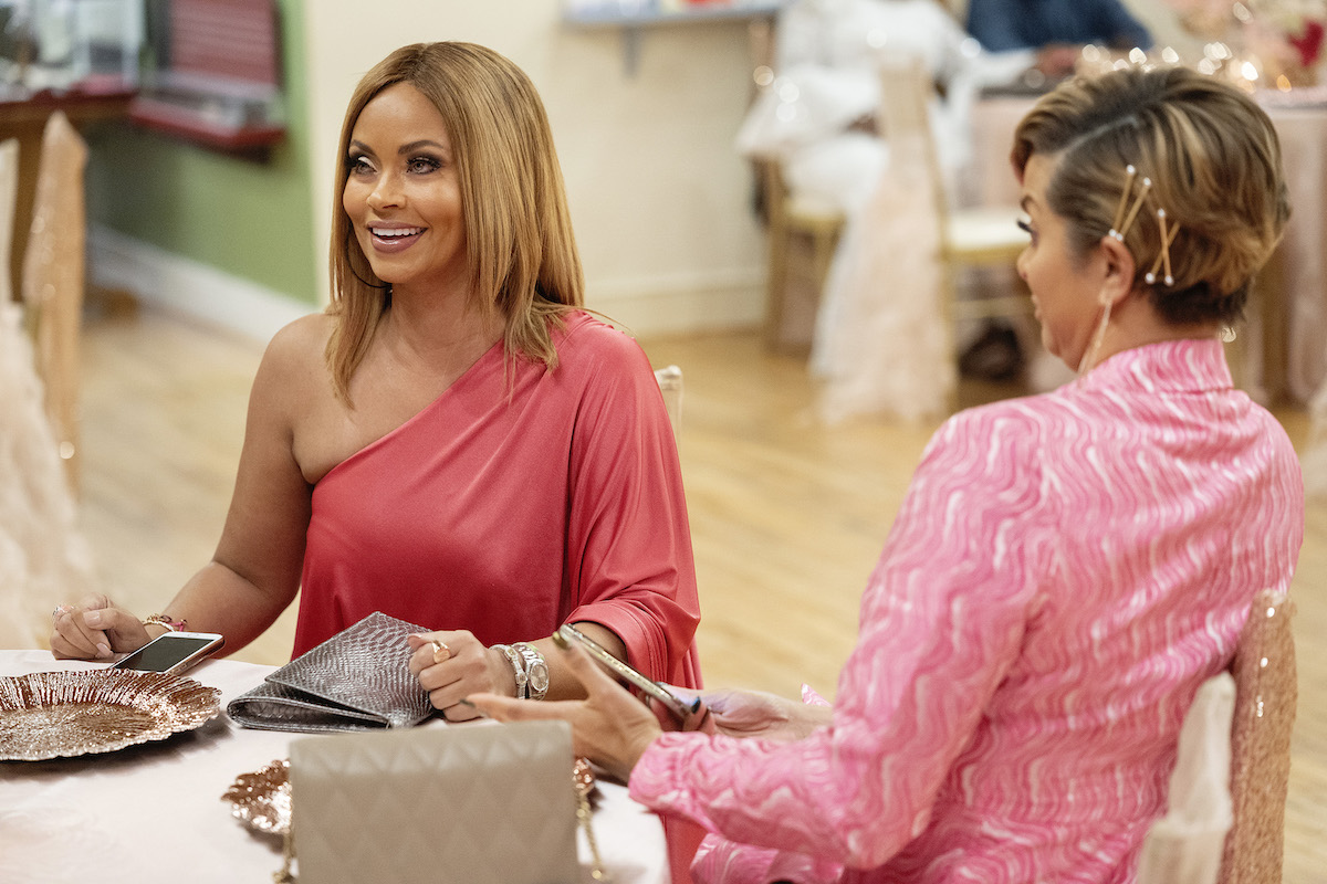 Gizelle Bryant smiles while sitting at a table next to Robyn Dixon on 'The Real Housewives of Potomac.'