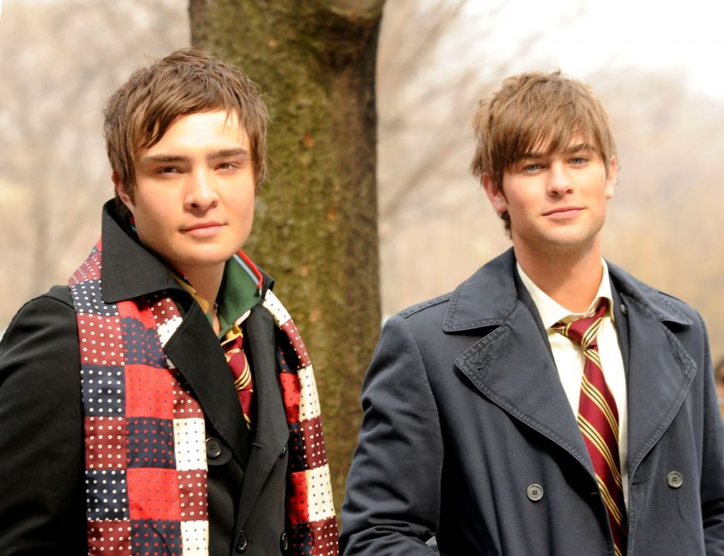 Ed Westwick as Chuck Bass wears a jacket and scarf and Chace Crawford as Nate Archibald wears a school uniform by a park in 'Gossip Girl'
