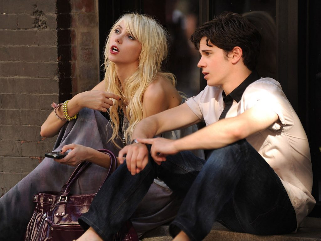 'Gossip Girl' stars Taylor Momsen as Jenny Humphrey and Connor Paolo as Eric van der Woodsen sits on the ground next to each other on the street.