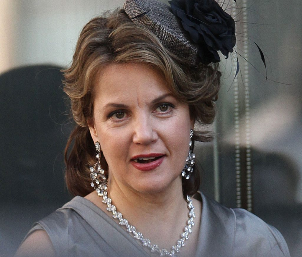 Margaret Colin has her hair up and makeup done to film 'Gossip Girl'. She wears pearls and dangling earrings.