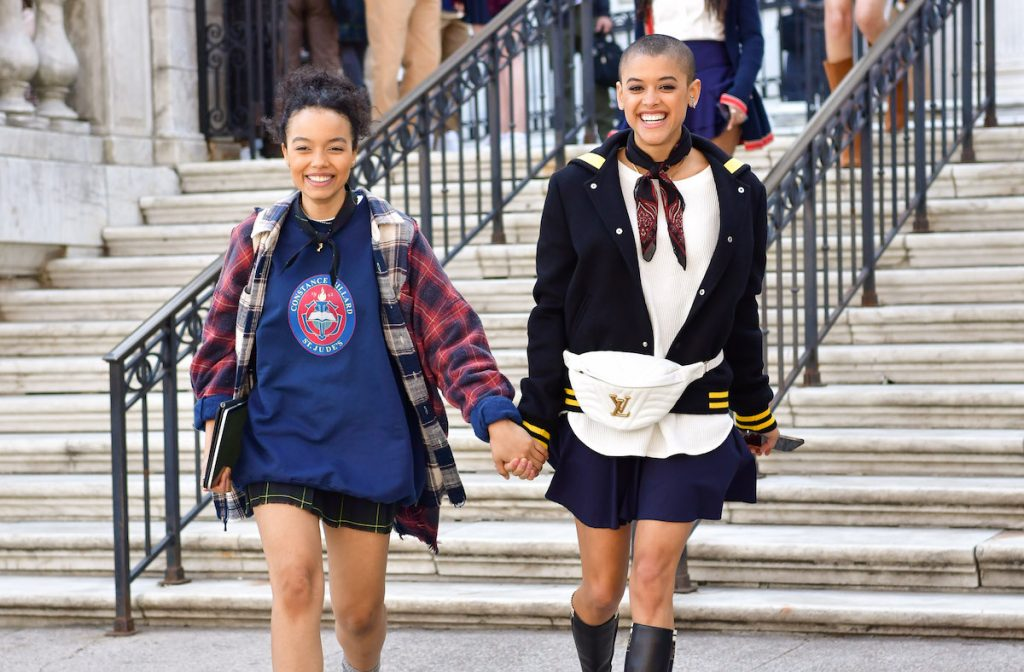 """Whitney Peak and Jordan Alexander hold hands on the set of """"Gossip Girl"""" in front of steps of a building."""