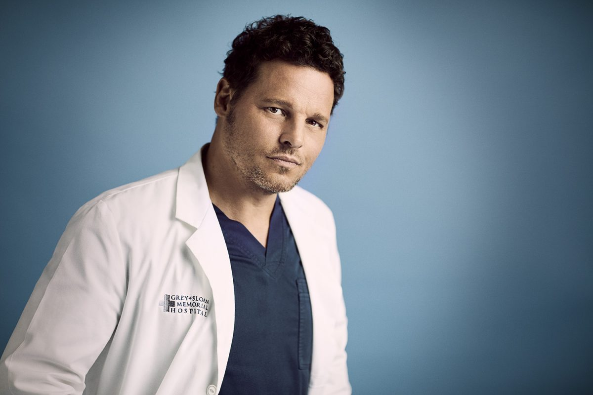 'Grey's Anatomy' actor Justin Chambers as Alex Karev wearing blue scrubs and smirking at the camera.