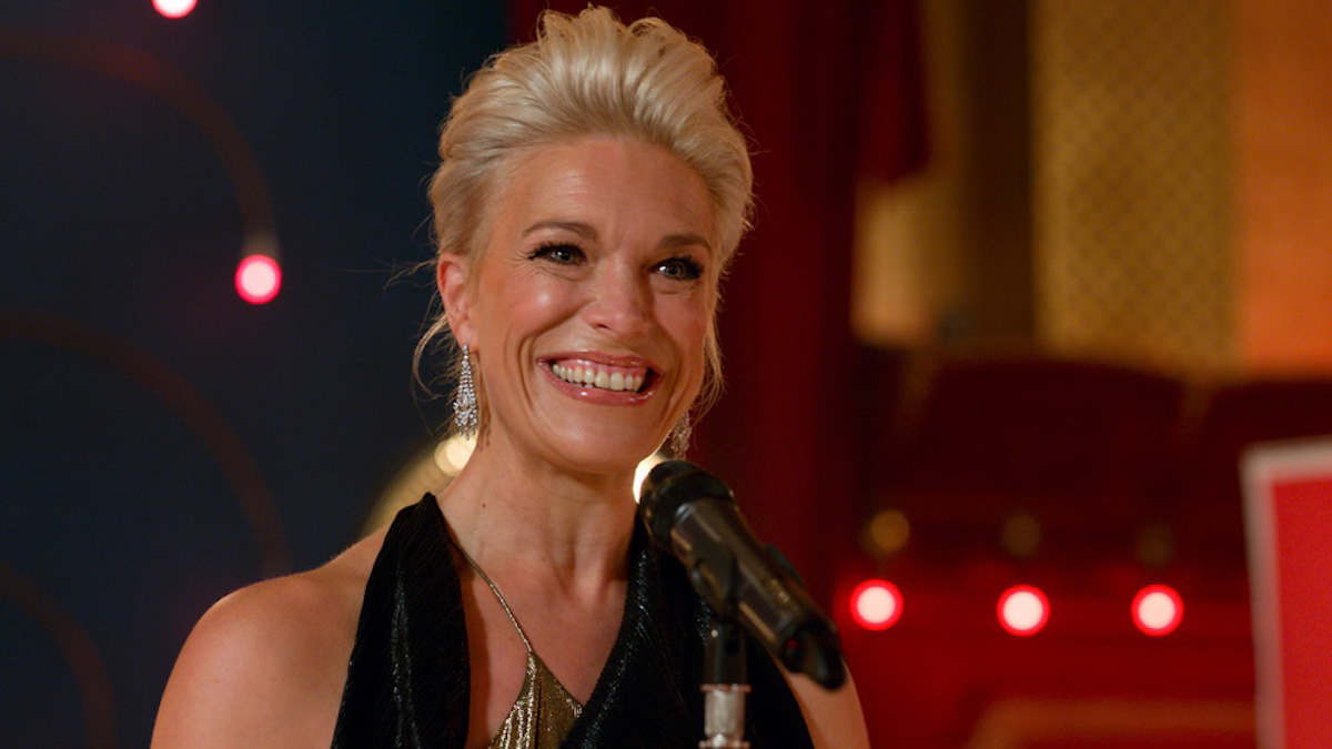 Hannah Waddingham as Rebecca Welton on 'Ted Lasso' standing in front of a microphone