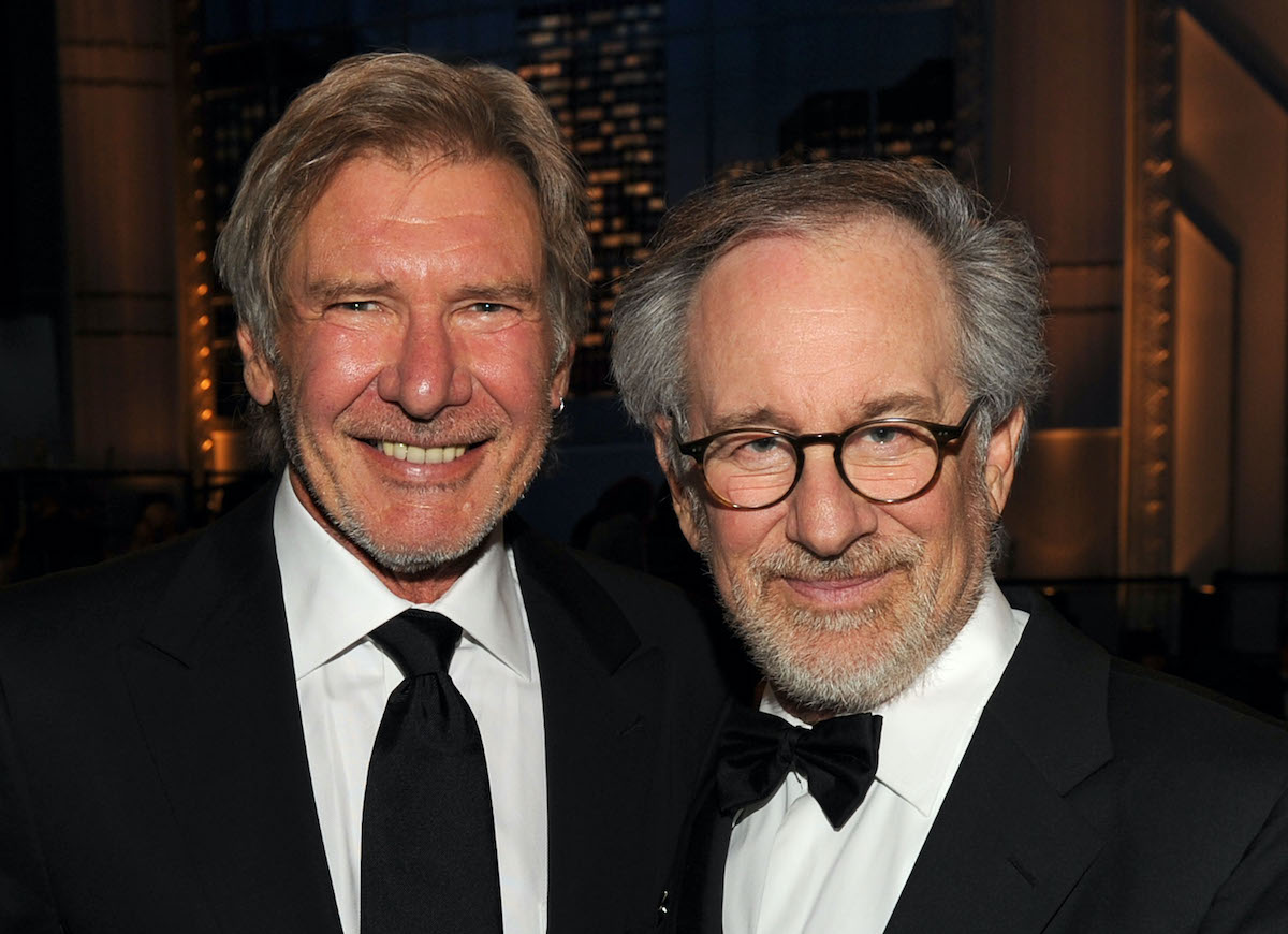 Harrison Ford and Steven Spielberg smile and pose while wearing suits