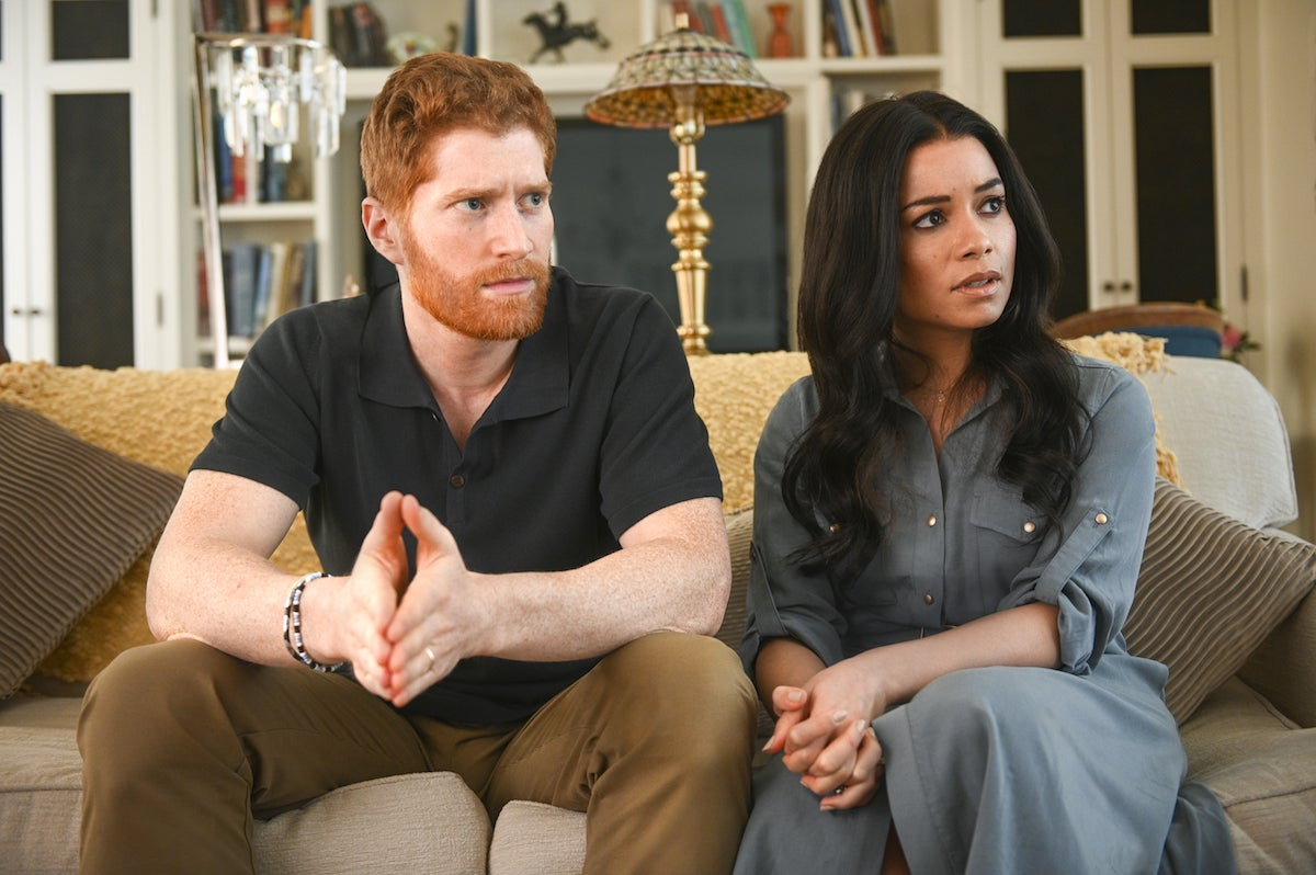 Harry and Meghan sitting on a couch in 'Harry & Meghan: Escaping the Palace'
