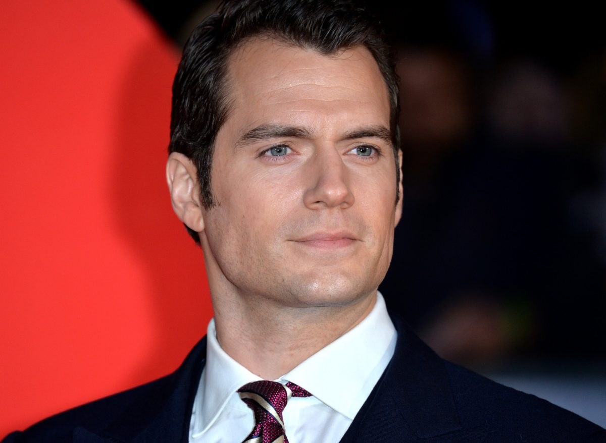 Henry Cavill wearing a black suit and red tie and standing in front of a black and red wall