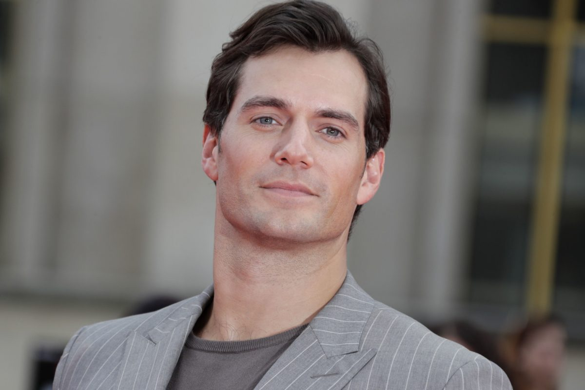 Henry Cavill wearing a grey suit and shit and smiling