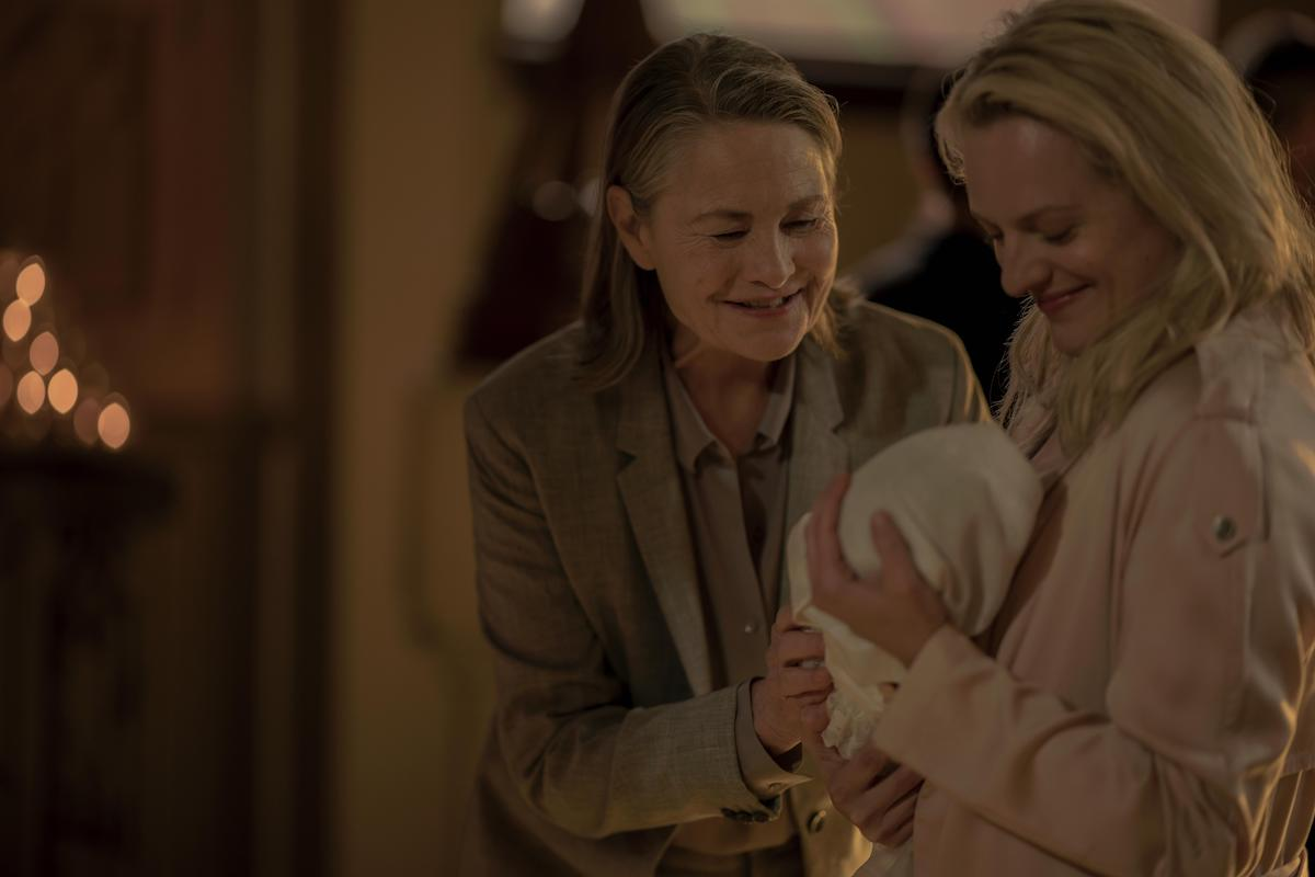 Holly (Cherry Jones) and June (Elisabeth Moss) in 'The Handmaid's Tale' Season 3. Moss wears a pink coat and holds a baby, who's wrapped in a white blanket. Jones wears a beige suit and smiles down at the baby. They're in a church for a baptism. The background is blurred.