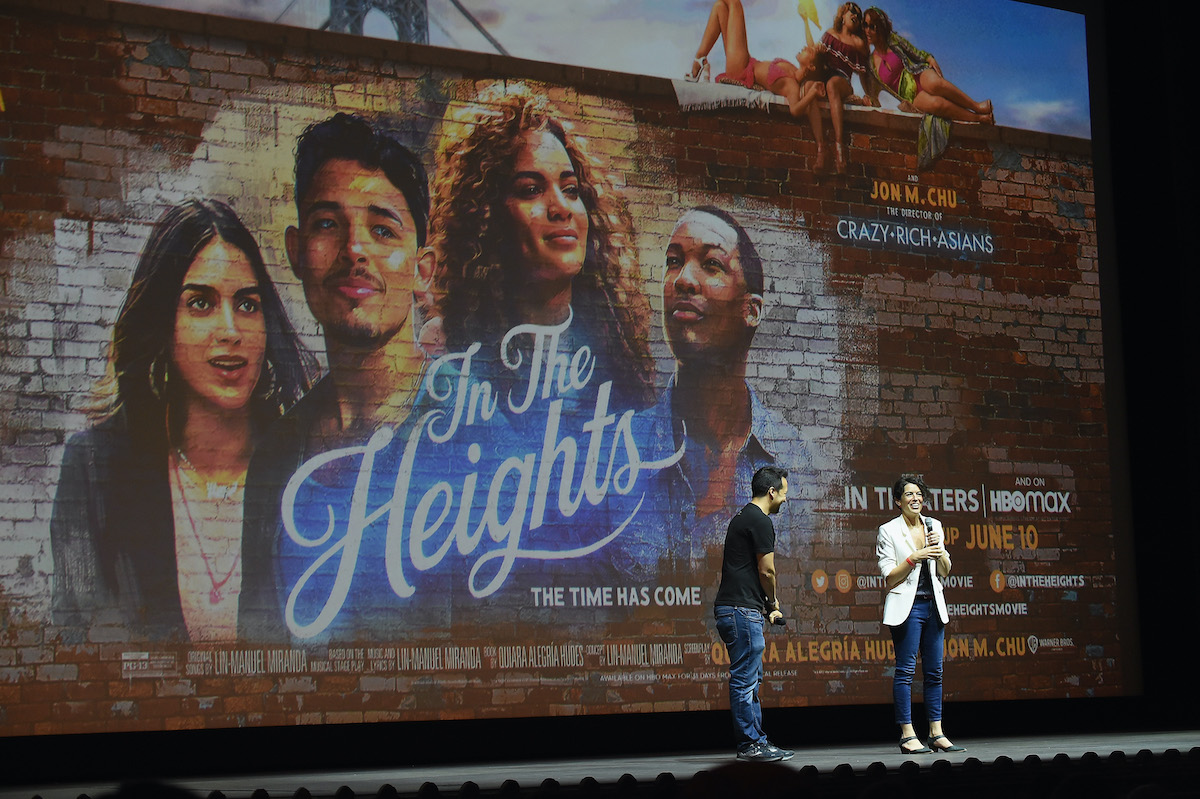 Lin-Manuel Miranda and Quiara Alegria Hudes speak onstage in front of a giant image of the 'In the Heights' poster