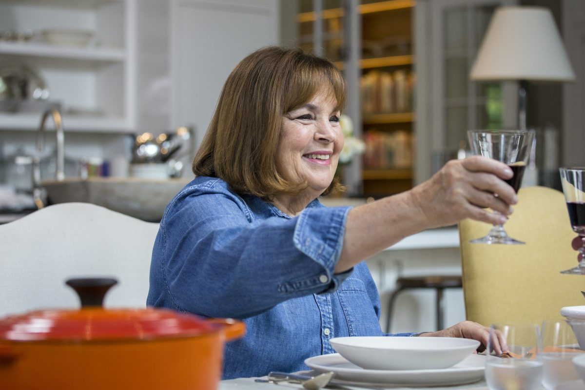 Ina Garten wears a blue shirt while smiling and toasting with a glass of wine