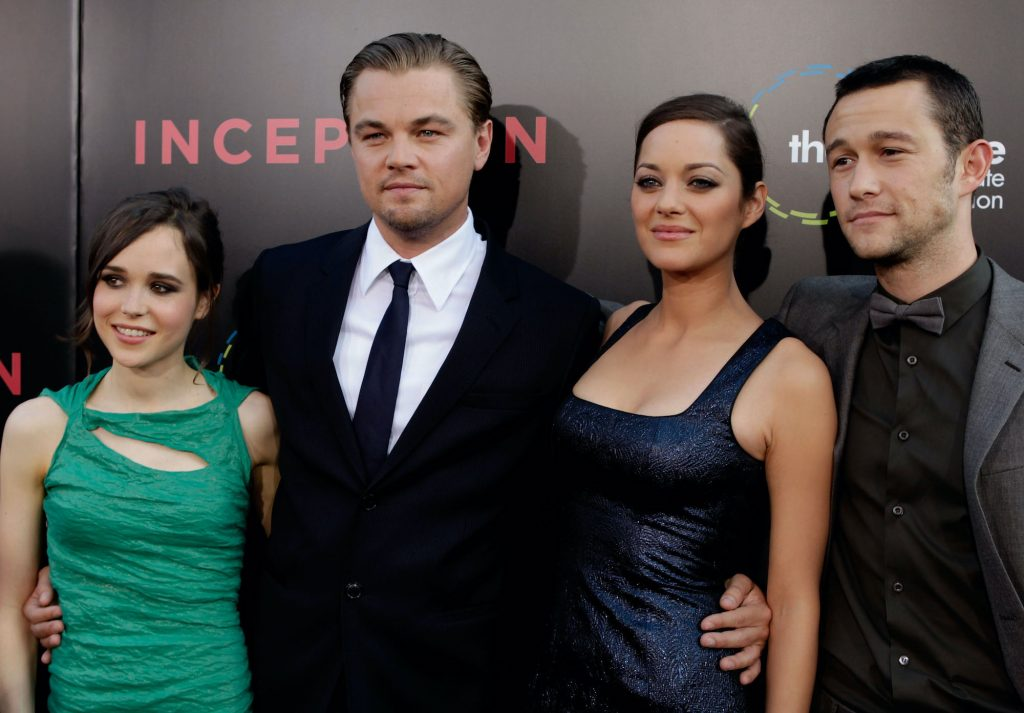 'Inception' cast smiling in front of a black background