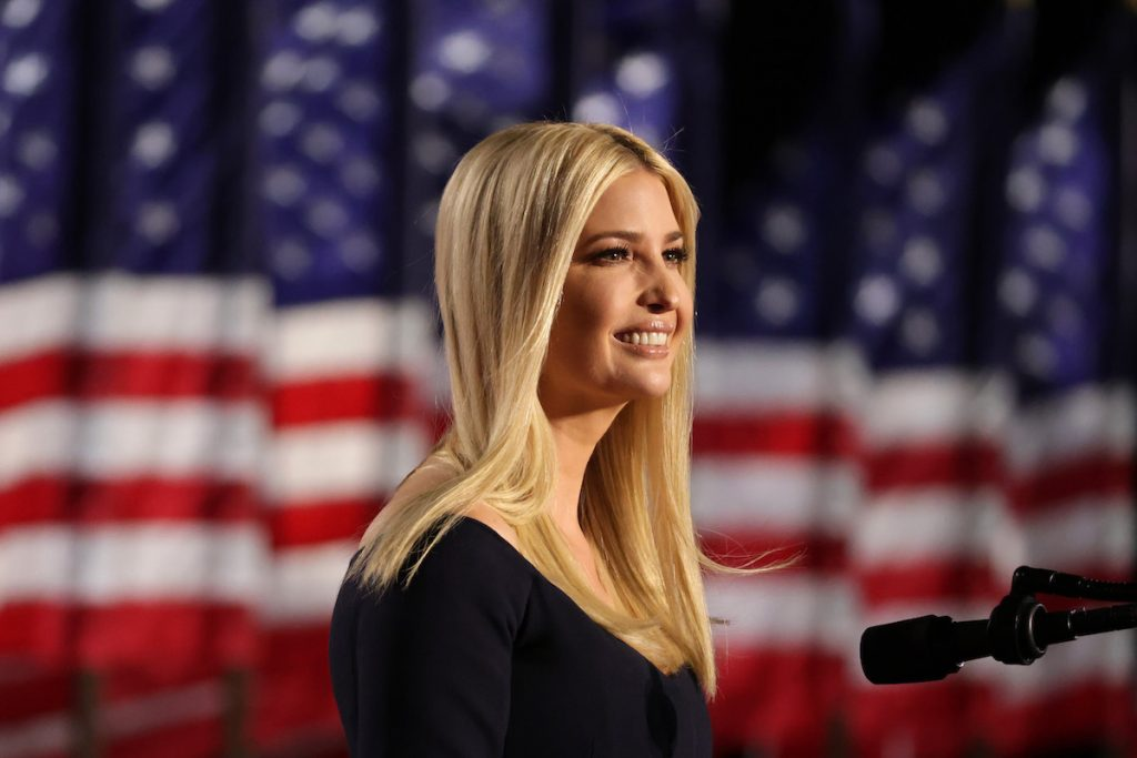 Ivanka Trump stands on stage smiling in front of an American flag.