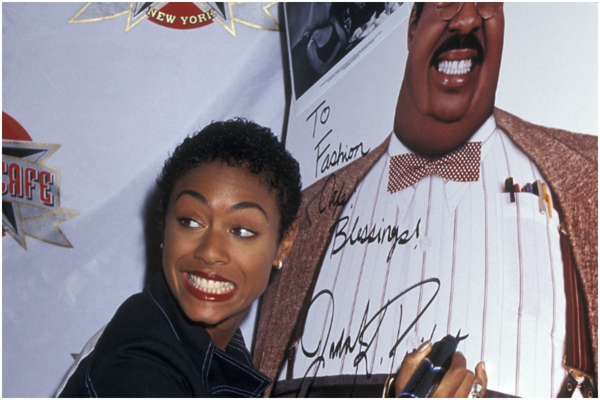 Jada Pinkett Smith smiling away from the camera while signing a 'The Nutty Professor' poster.