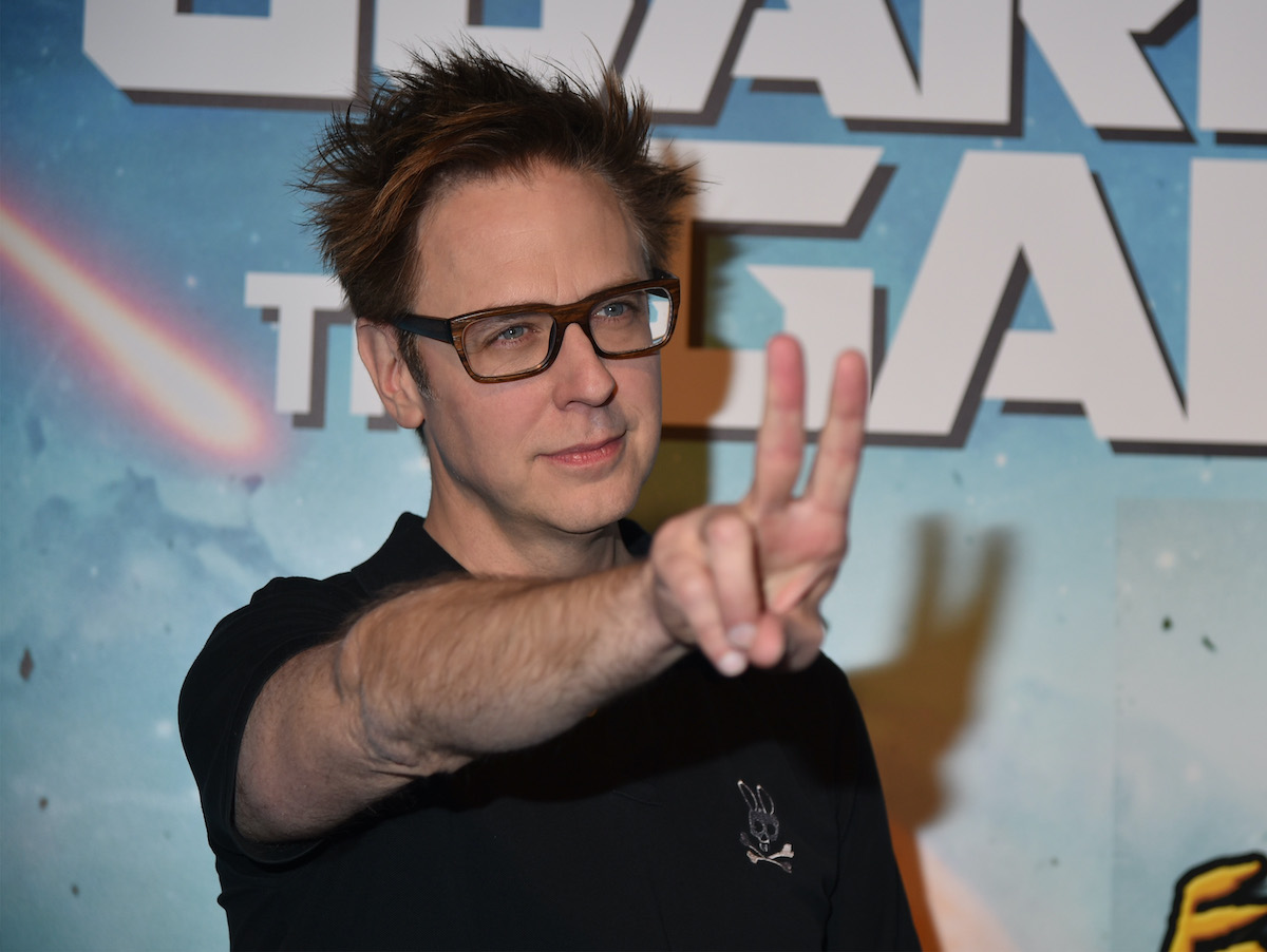 James Gunn holds two fingers up as he poses on the red carpet