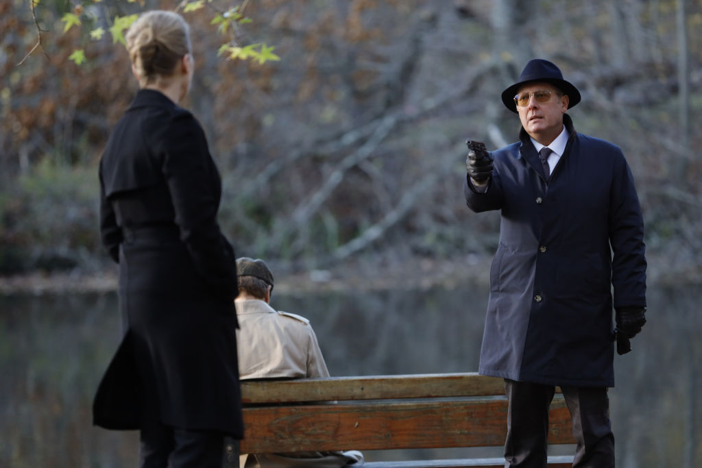 Laila Robins as Katarina Rostova stands outside while James Spader as Raymond 'Red' Reddington points a gun at her.