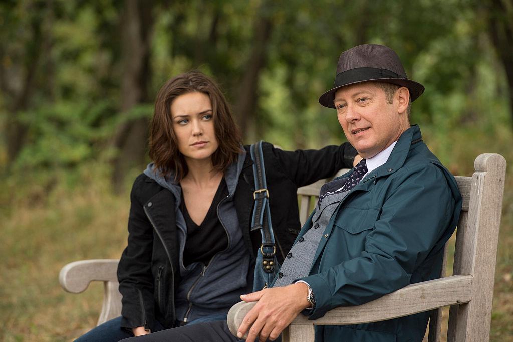 Megan Boone as Elizabeth Keen, James Spader as Raymond 'Red' Reddington sit on a park bench together.