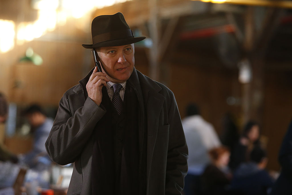 James Spader as Raymond 'Red' Reddington stands outside on his cellphone with a concerned look on his face.