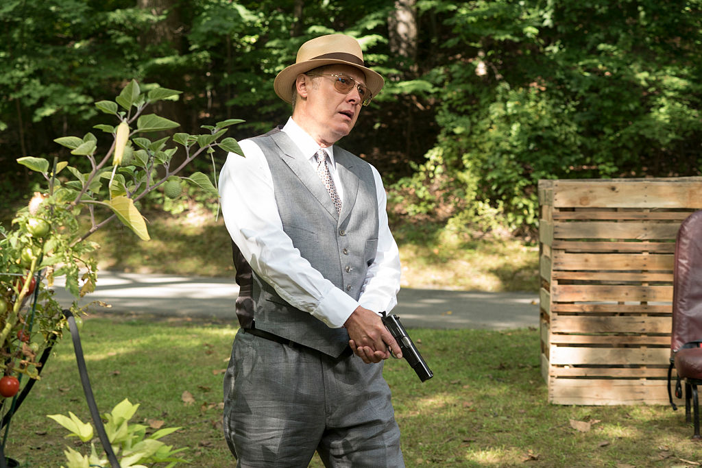 James Spader as Raymond 'Red' Reddington hides outside with his gun drawn. He's wearing a tan fedora, sunglasses, vest, nice slacks, and a white button-up shirt.