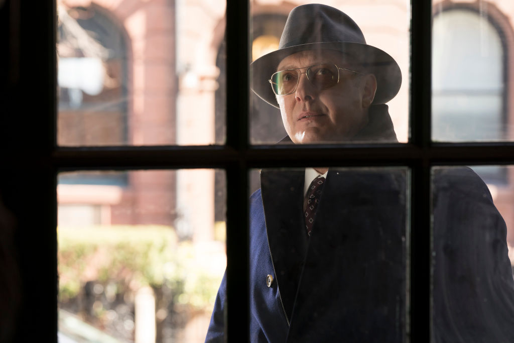 James Spader as Raymond 'Red' Reddington  looks through a window from the outside. He's wearing a trench coat, fedora, and sunglasses.