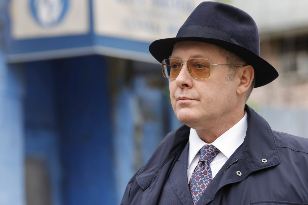 James Spader as Raymond 'Red' Reddington stands outside in his trademark navy fedora, sunglasses, and trenchcoat.