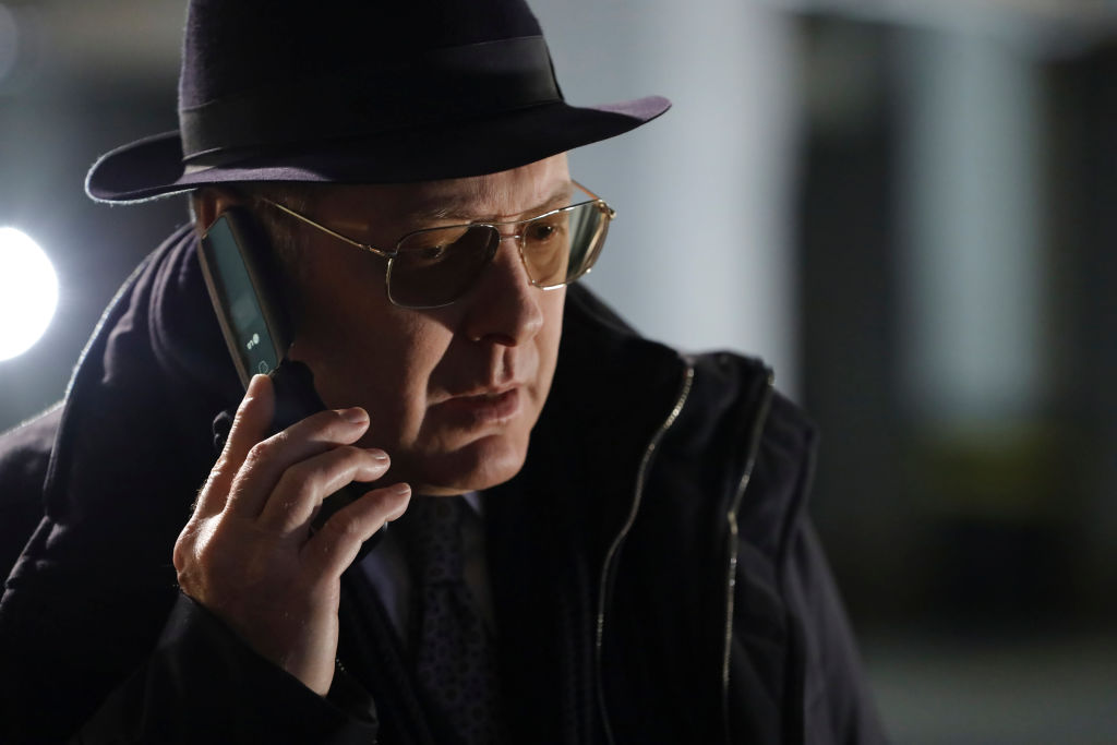 James Spader as Raymond 'Red' Reddington is wearing his classic fedora and glasses while speaking on the phone.
