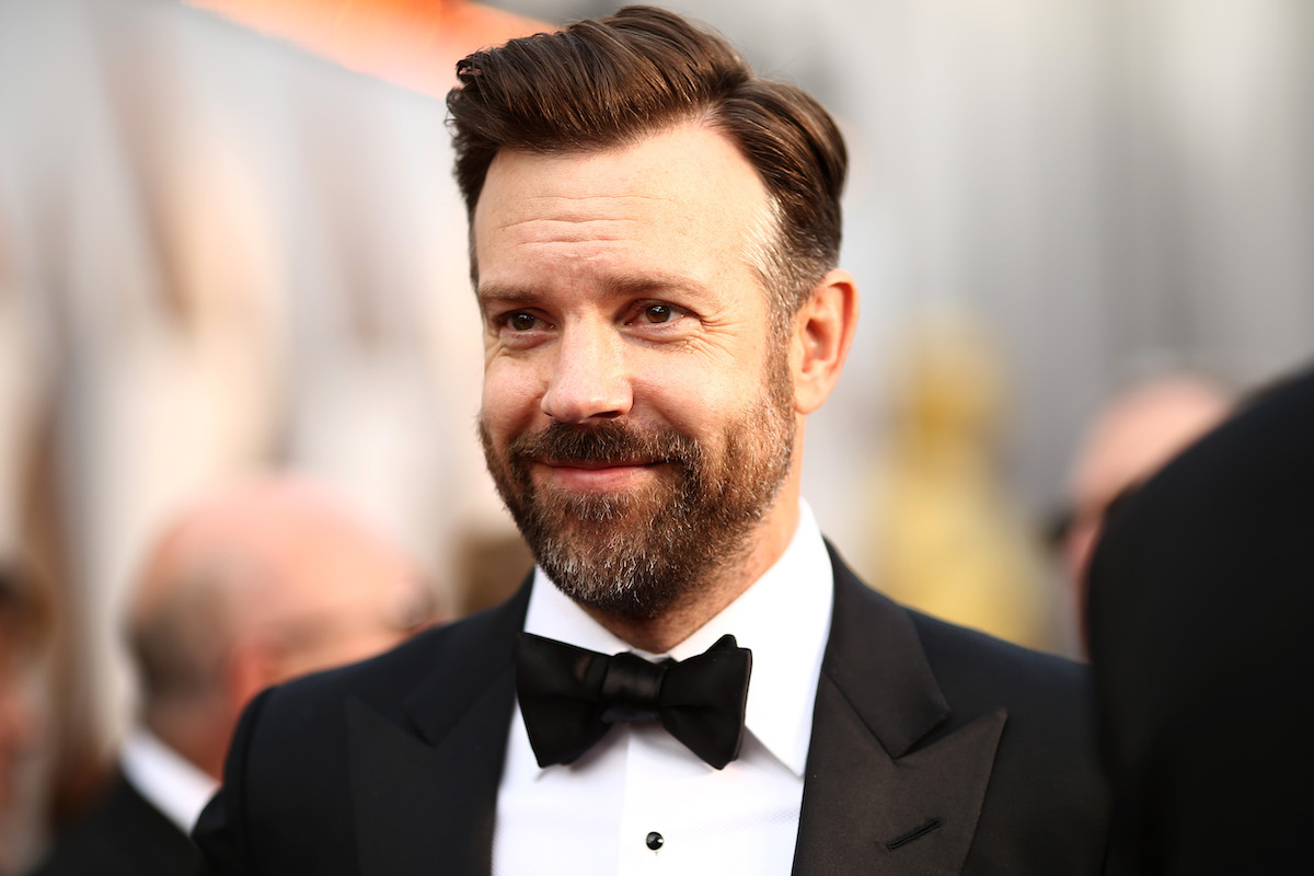 Jason Sudeikis smiles on a red carpet in a black suit and bow tie.
