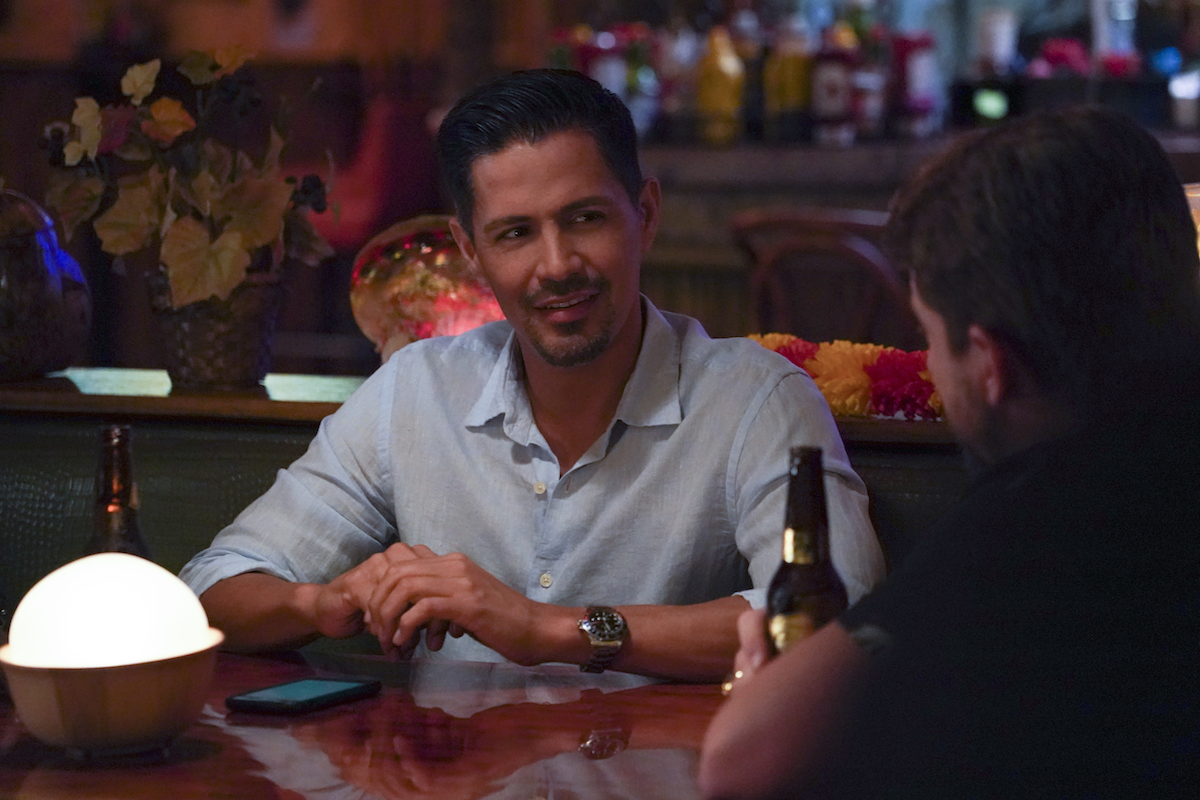 Jay Hernandez sitting at a table in 'Magnum PI' episode